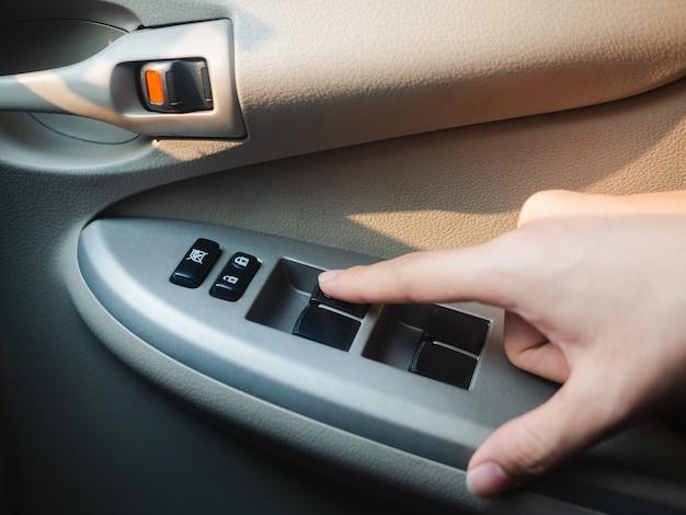 Closeup driver's hand pressing car window controls button.