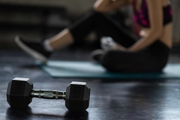 흐림 운동선수 여성이 있는 근접 촬영 아령은 피트니스 스포츠 체육관에서 운동한 후 휴식을 취합니다. 웨이트 트레이닝, 보디 빌딩 및 건강한 스포츠 라이프 스타일 개념.