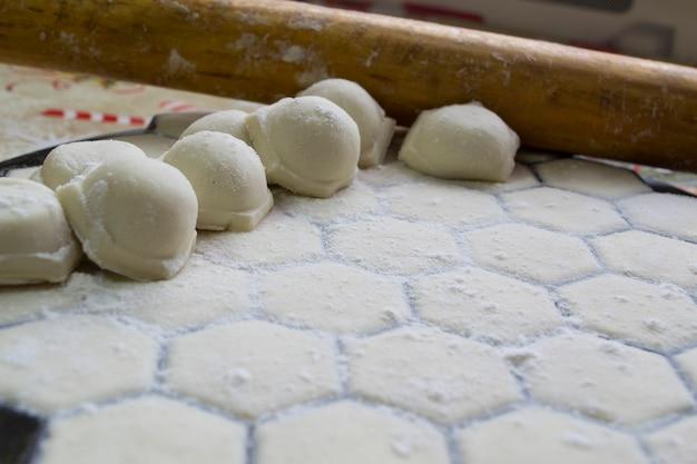 Closeup of dumplings on the background of a rolling pin handmade dumplings