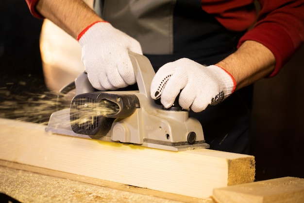Closeup of electric plane throws sawdust while woodworker making wooden detail on workbench at cottage workshop