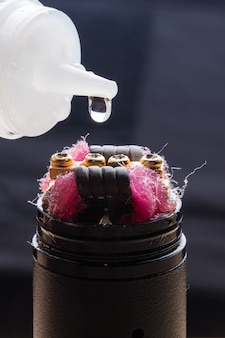 Closeup of an electronic cigarette with a drop of liquid