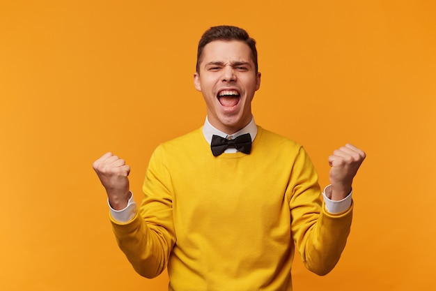 Closeup of emotional man isolated on yellow wall showing white teeth while screaming