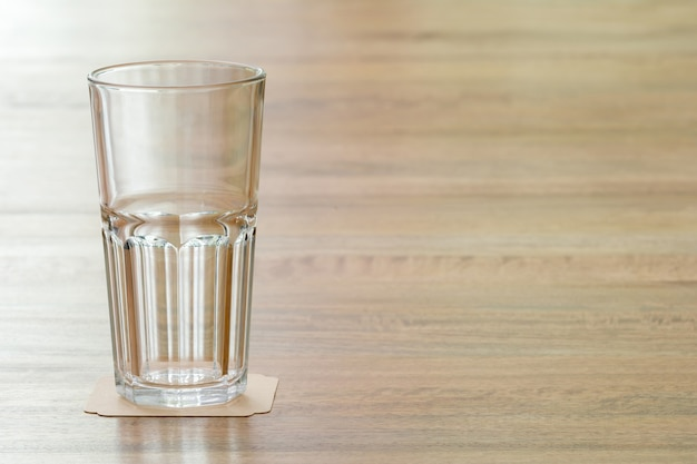 Closeup empty glass on wooden table, meaning a positive attitude towards something and prompt to learn anything