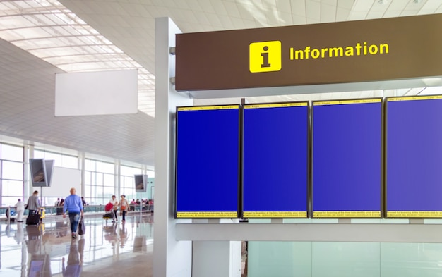 Closeup of empty information panel flight times in the airport with defocused passengers walking in the background