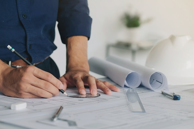 Closeup of engineer hand drawing plan on blue print with architect equipmentarchitectural plan