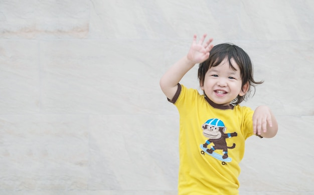 Closeup enjoy asian kid with smile face on marble stone wall textured background