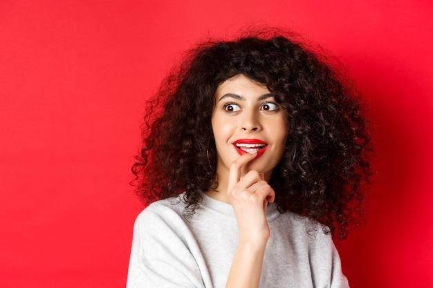 Primo piano di una donna riccia eccitata che tocca le labbra e guarda da parte con interesse controllando una bella promo...