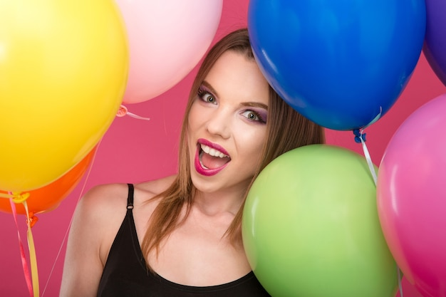 Closeup of excited happy smiling raptures glamour young female with pinklips with colorful balloons