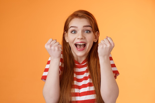 Closeup excited hopeful redhead lucky girl winning first prize score goal smiling broadly receive ex...