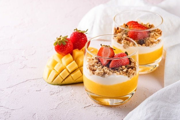 Closeup exotic breakfast with mango, cottage cheese and granola decorated with strawberries. concept of healthy and tasty desserts