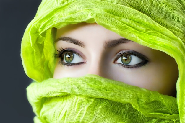 Closeup of the eyes of a woman with a green hijab under the lights