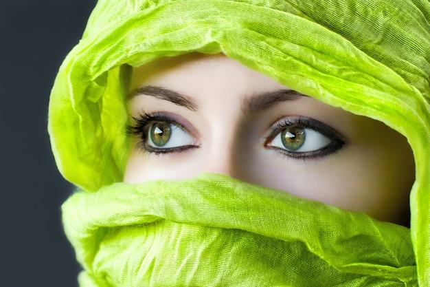Primo piano degli occhi di una donna con un hijab verde sotto le luci