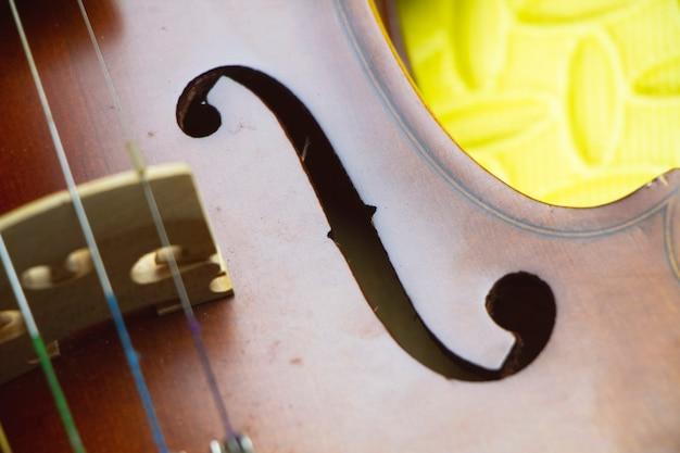 F-отверстие крупным планом на лицевой стороне скрипки, размытый свет вокруг