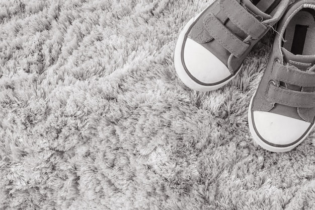 Closeup fabric sneakers of kid on gray carpet textured background