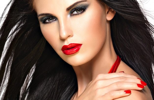 Closeup face of a beautiful brunette woman with red nails and lips