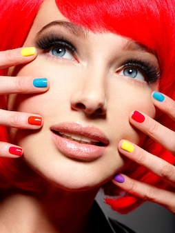 Closeup face of a beautiful  girl with bright multicolor nails.