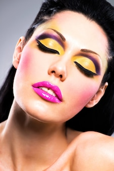 Closeup face of beautiful woman with fashion bright colour makeup