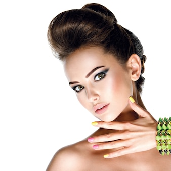 Closeup face of beautiful woman with multicolored nails.