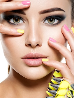 Closeup face of beautiful woman with multicolored nails