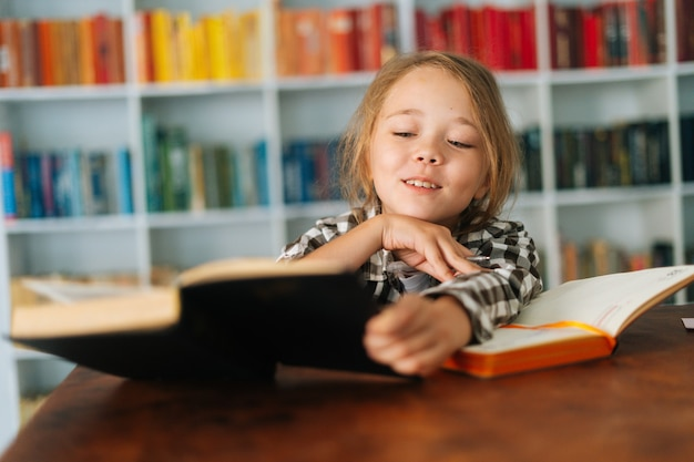 Closeup face of cheerful pupil school girl kid doing homework reading paper book sitting at table in