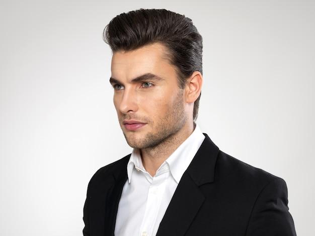 Fronte del primo piano di un giovane uomo d'affari di modo in pose casuali del vestito nero allo studio