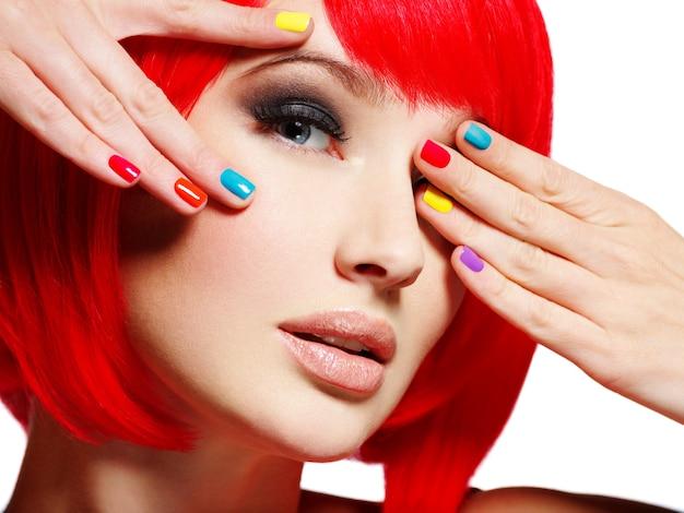 明るい多色の爪を持つ美しい少女のクローズアップの顔。