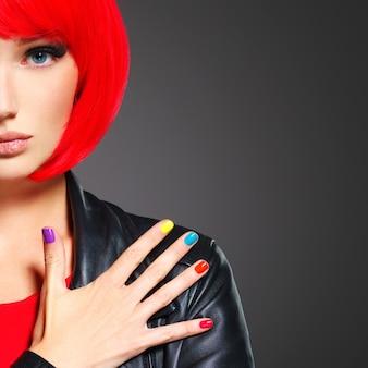 밝은 여러 가지 빛깔의 손톱으로 아름 다운 여자의 근접 촬영 얼굴.