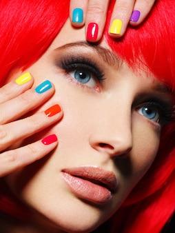 Крупным планом лицо красивой девушки с яркими разноцветными ногтями.