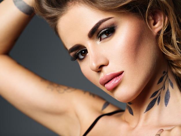 Крупным планом лицо красивой сексуальной девушки с татуировкой на шее.