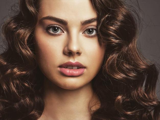 연기가 자욱한 눈 화장과 아름 다운 여자의 근접 촬영 얼굴. 긴 곱슬 머리를 가진 섹시하고 화려한 갈색 머리 여자. 포즈를 취하는 매력적인 여성의 초상화입니다.