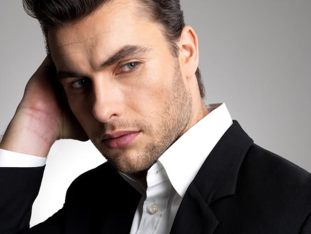 スタジオで黒のスーツのカジュアルなポーズでファッション青年実業家のクローズアップの顔