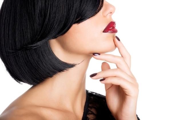 美しいセクシーな赤い唇と暗い爪を持つ女性のクローズアップの顔