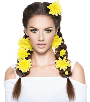明るい黄色のメイクで若い美しい女性のクローズアップの顔。ファッションの肖像画。スタイリッシュな髪型、おさげ髪の魅力的な女の子-白で隔離。プロのメイク。アートヘアスタイル。