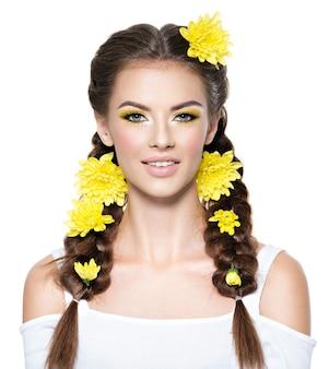 Крупным планом лицо молодой улыбающейся красивой женщины с ярко-желтым макияжем портрет моды привлекательная девушка с косичками стильная прическа, изолированные на белом профессиональный макияж