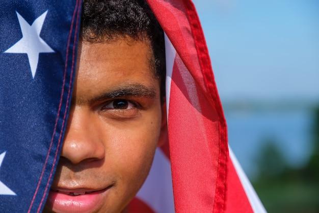 행복한 아프리카계 미국인 남자의 클로즈업 얼굴이 미국 국기에 싸여 있다