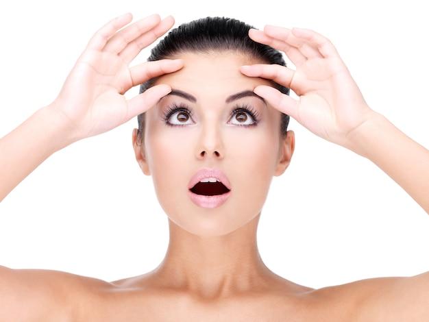 若いきれいな女性のクローズアップの顔は額に肌を絞る