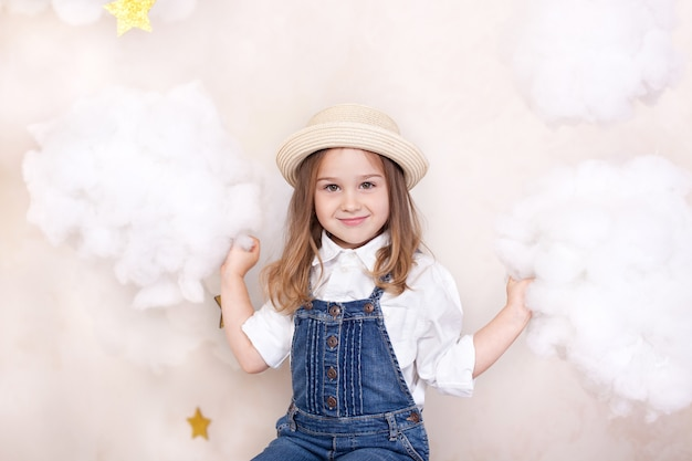 Closeup face portrait of cute little girl in straw hat. smiling child flies in sky with clouds and stars. little astrologer. little traveler. concept of preschool education of child. child is dreaming