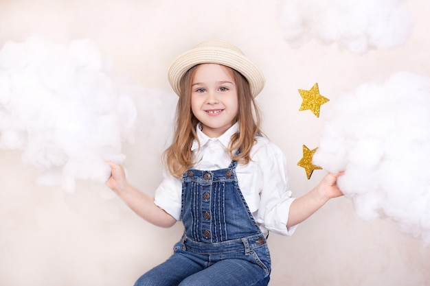 Closeup face portrait of cute little girl in straw hat. smiling child flies in sky with clouds and stars. little astrologer.