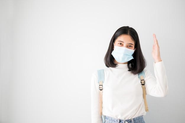クローズアップの顔の肖像画女子大生アジアの学生はマスクを着用し、学校の時間中は社会的距離を保ちます。