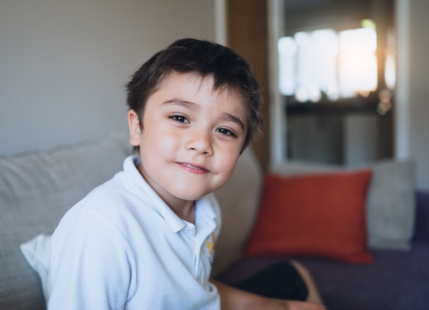 Closeup face schoolboy looking at camera with smiling face, happy child relaxing at home after back from school, indoor portrait positive kid sitting on sofa in living room