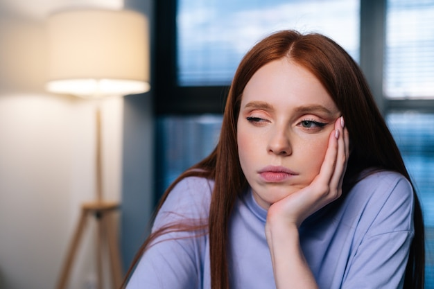 Closeup face of tired sad woman sitting at desk with laptop in office room near window at night