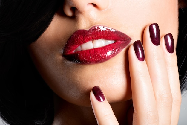 Closeup face of a woman with beautiful sexy red lips and dark nails