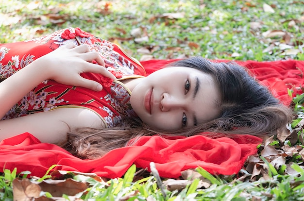 Closeup face of young beautiful lady wearing chinese red dress,looking straight,portrail of model posing,in a garden