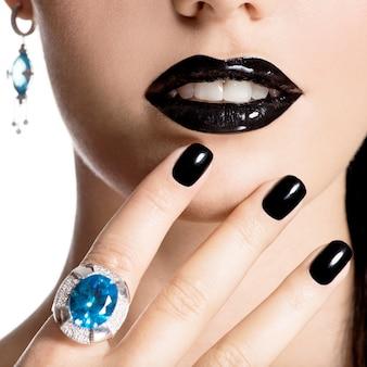 Fronte del primo piano di giovane bella donna con manicure nera e trucco luminoso di moda