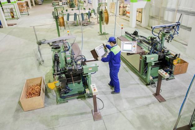 クローズアップ工場労働者は、エアコンのラジエーターのために銅管をカットします