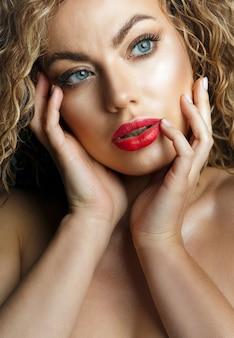 赤い唇と裸の肩でポーズをとって巻き毛の魅力的な若い女性のクローズアップファッションの肖像画