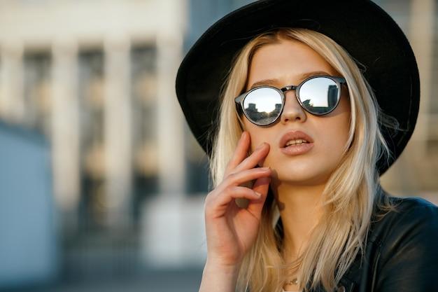 모자, 거울 안경 및 가죽 재킷을 입고 멋진 여자의 근접 촬영 패션 초상화. 텍스트를 위한 공간