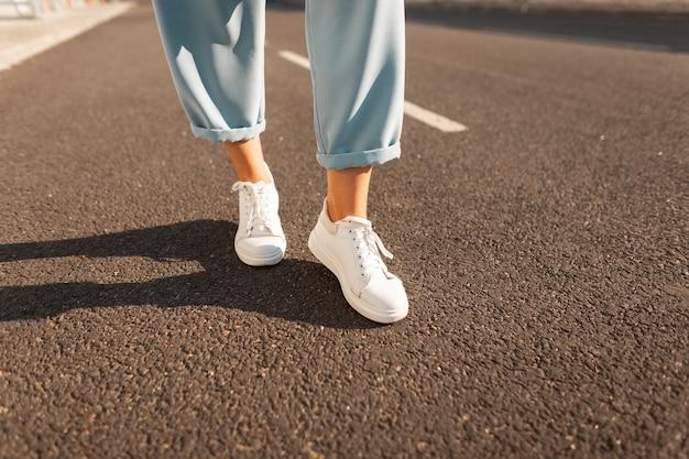 白いトレンディなスニーカーのスタイリッシュな青いズボンのクローズアップファッショナブルな女性の脚は、明るい晴れた日にアスファルトの上に立っています。ファッショナブルでモダンな夏のレディースシューズコレクション。カジュアルスタイル。