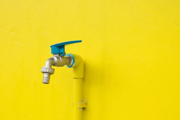 Closeup faucet on concrete yellow wall background. water leaking, saving concept.