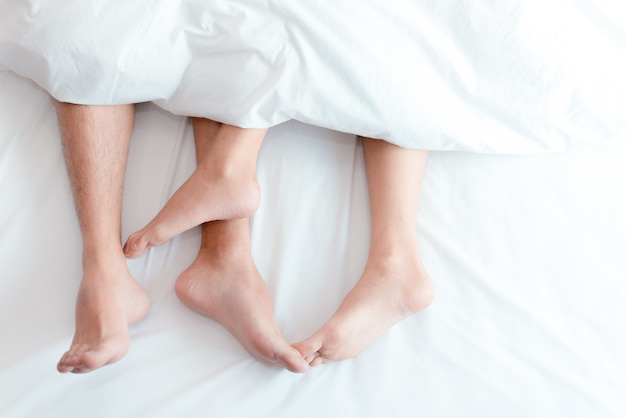 Closeup feet of couple on the bed